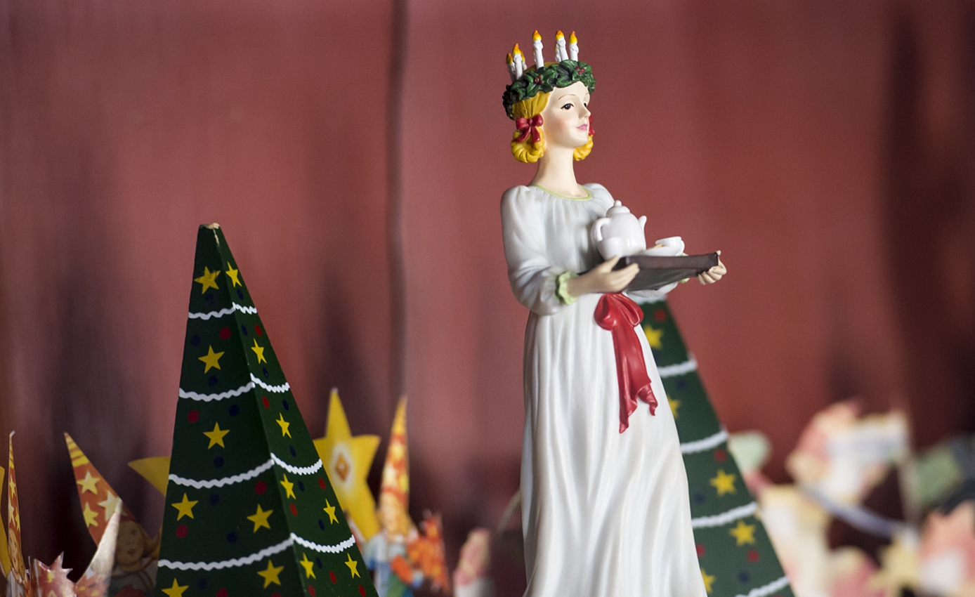 A doll in white next to green decorated trees