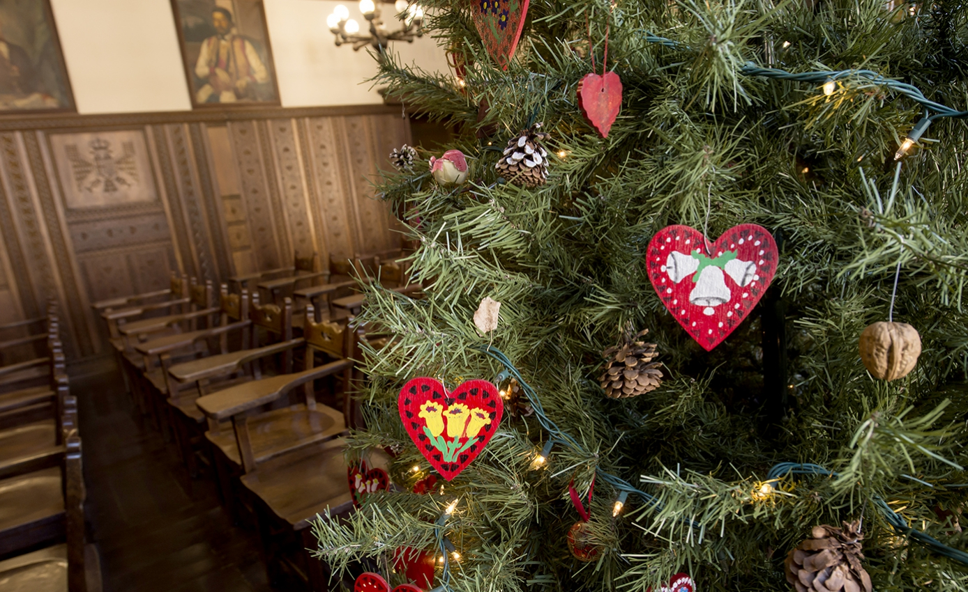 A tree with red ornaments in front of a classroom