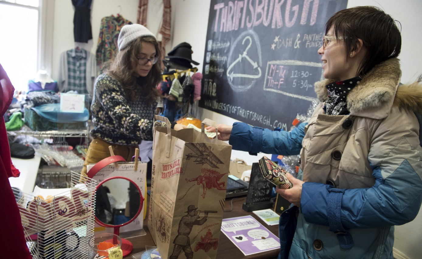 "A person in a tan and blue coat hands money to a cashier in a gray beanie and multicolored sweater beneath a sign that reads: ""Thriftsburgh."""