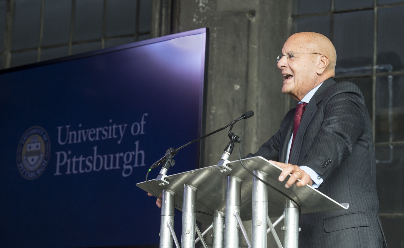 Jeffrey Romoff speaks from a podium with University of Pittsburgh sign in background