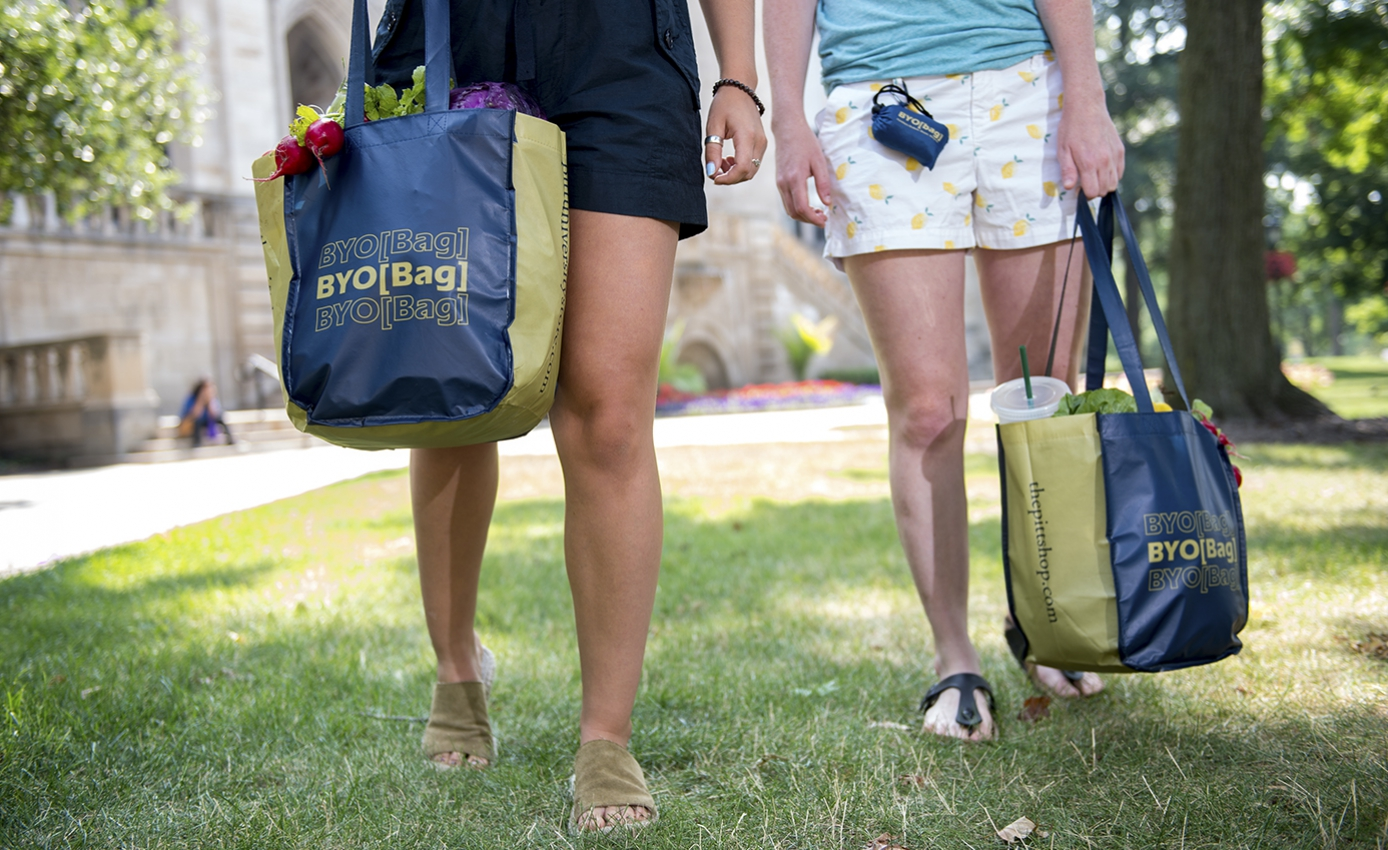 Two people, seen from the waist down, carry blue BYO[Bag] bags while walking on a grass lawn.