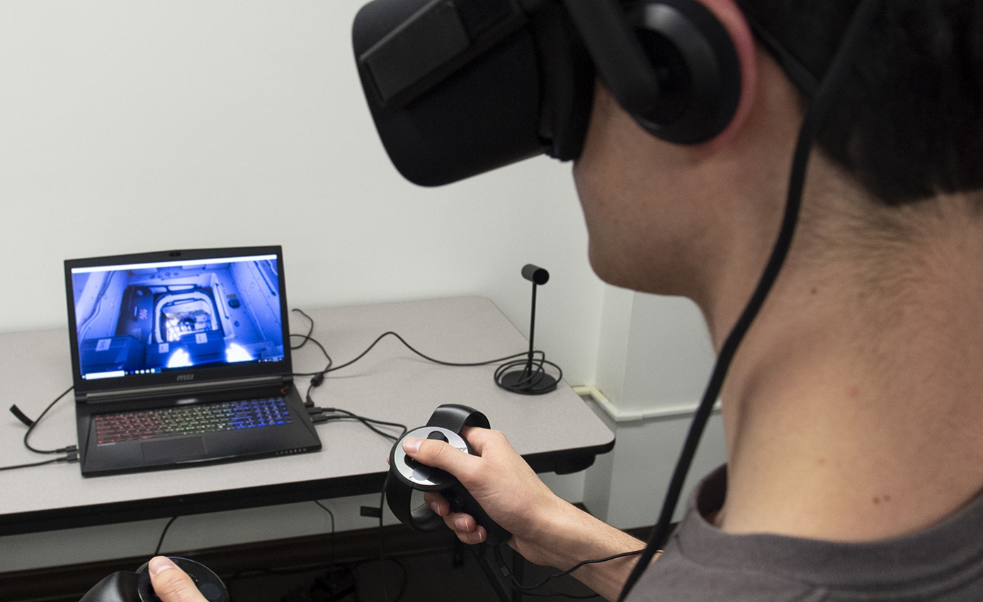 man wearing a VR headset and looking toward a laptop