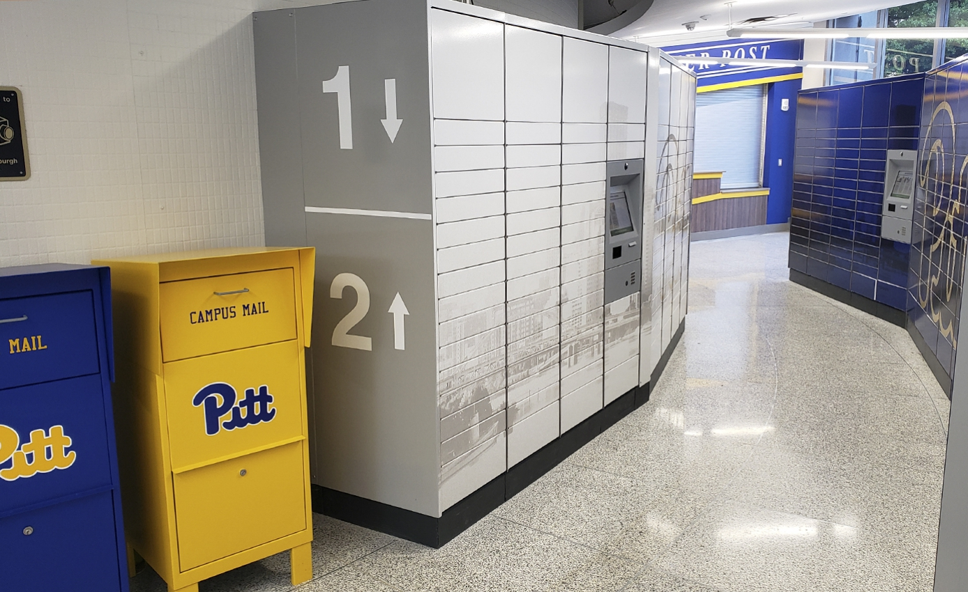Blue and gold script-Pitt branded campus mail collection bins and larger, computerized mailboxes.