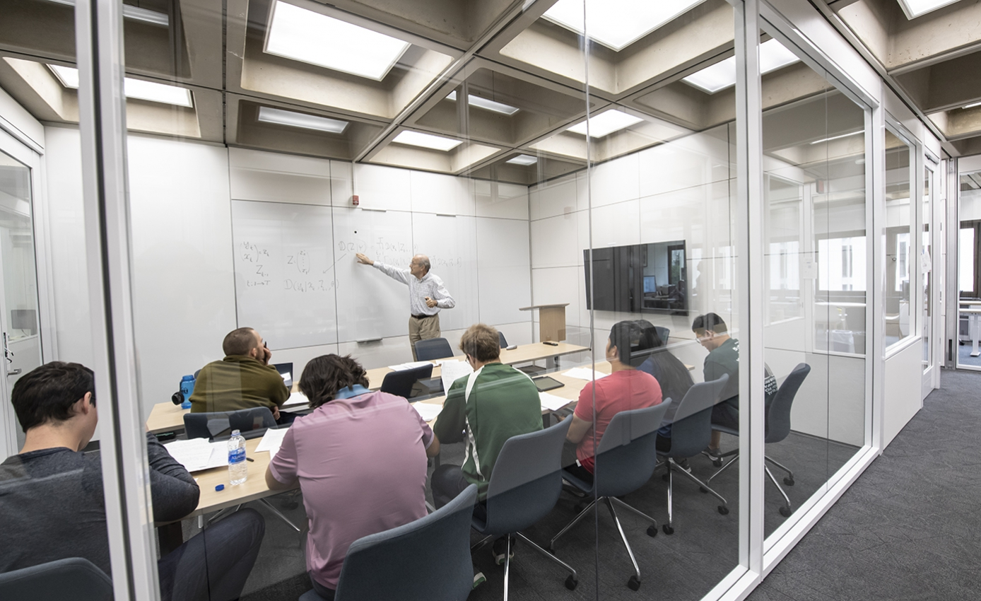 Professor gesturing toward whiteboard while teaching before a room of students sitting a long tables in a glass-walled classroom