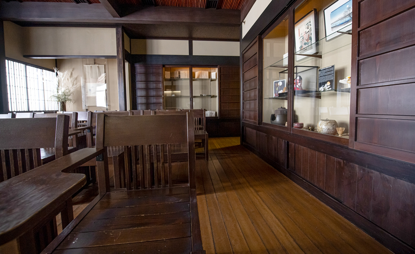 A wooden room with desks and chairs