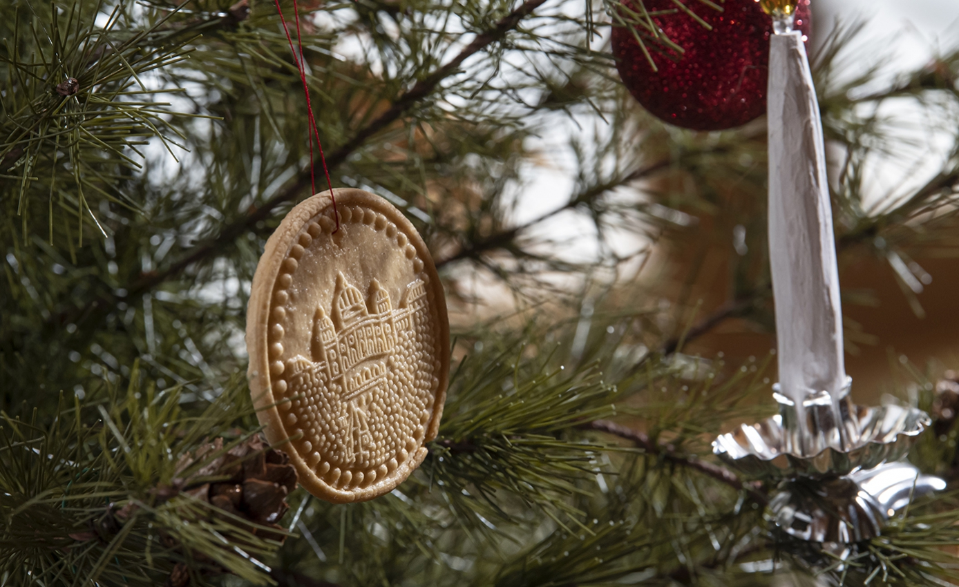 A gold colored round ornament on a tree