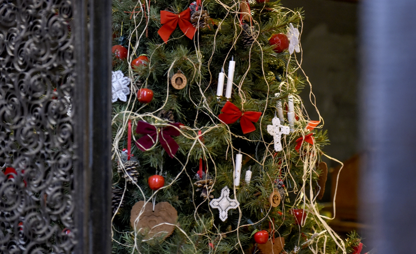 A tree draped in ornaments including red bows and white crosses