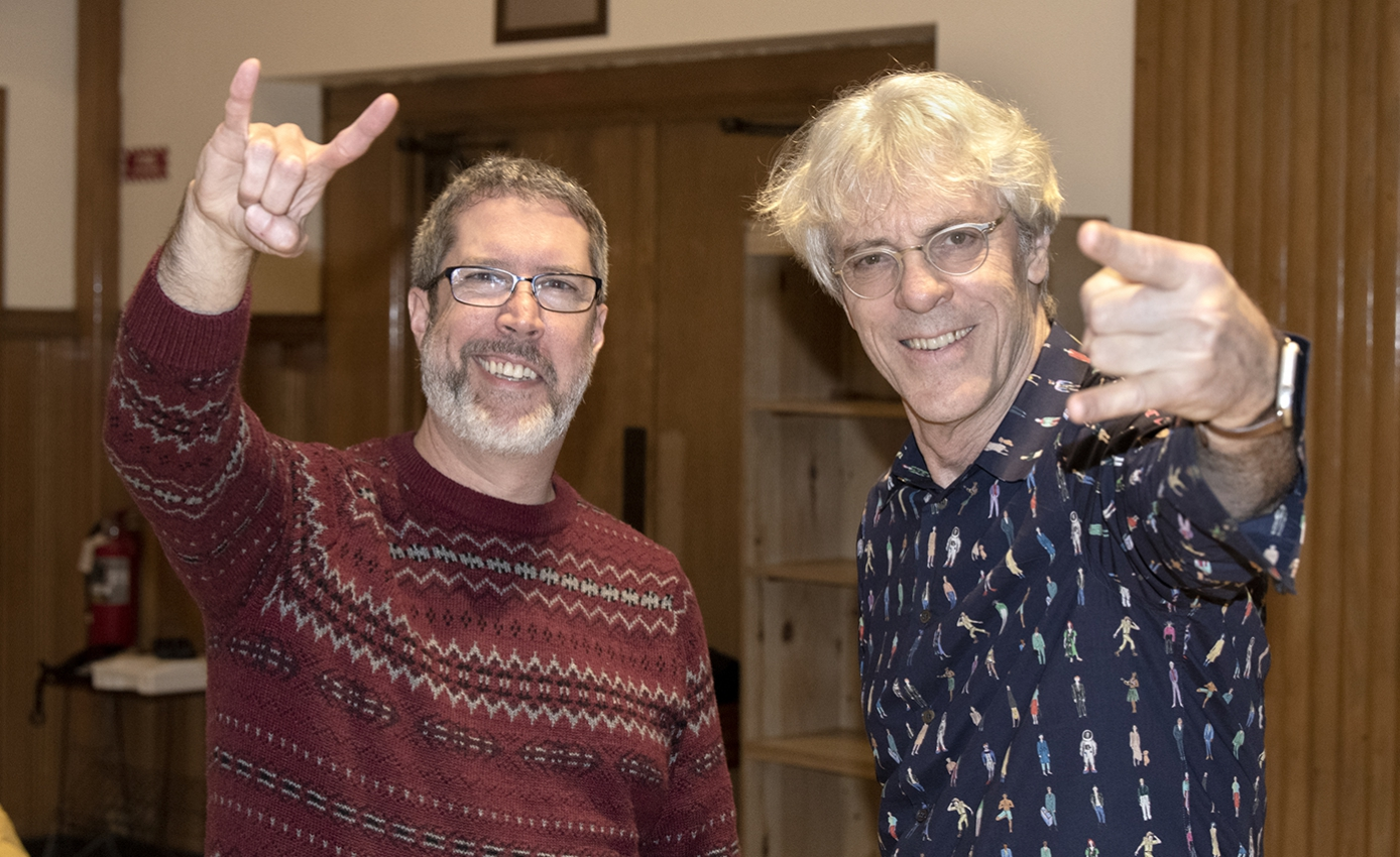 Scott O'Neal in a red sweater next to Stewart Copeland in a blue collared shirt