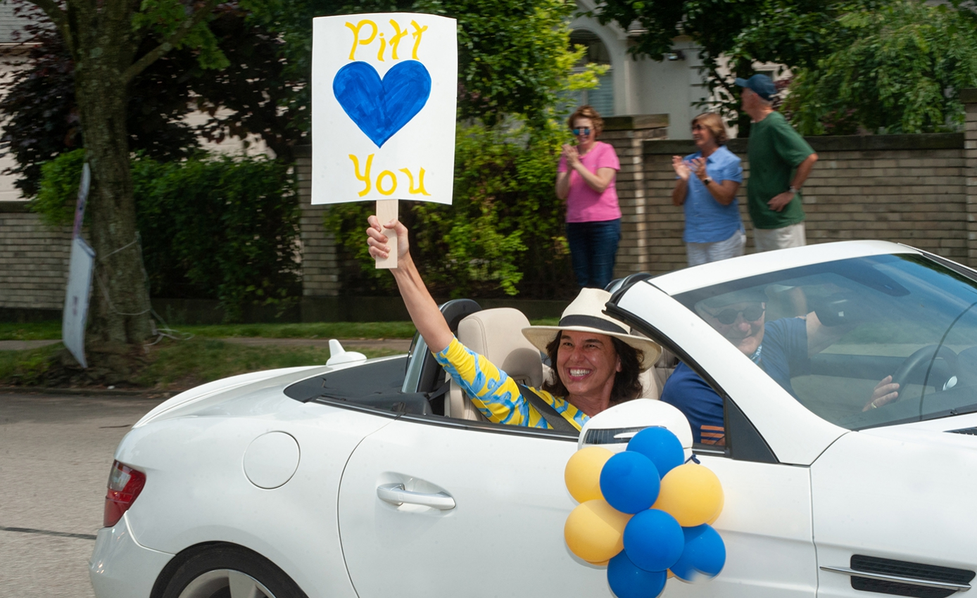 "A woman in a hat raises a blue and gold ""Pitt Loves You"" sign"