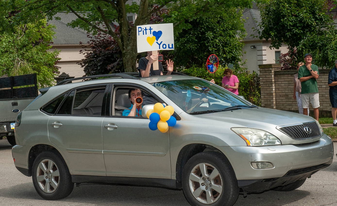 """A person in a silver SUV plays the bugle while another raises a """"Pitt Loves You"""" sign through the sun roof"""