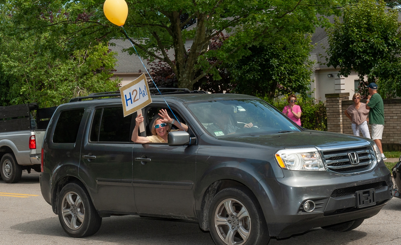 "A woman in a yellow top drives by with an ""H2Art"" sign and a yellow balloon"