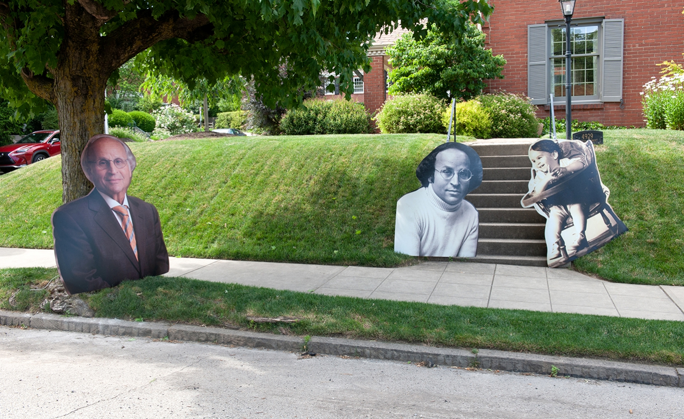 Photo cutouts of Art Levine spread across a lawn