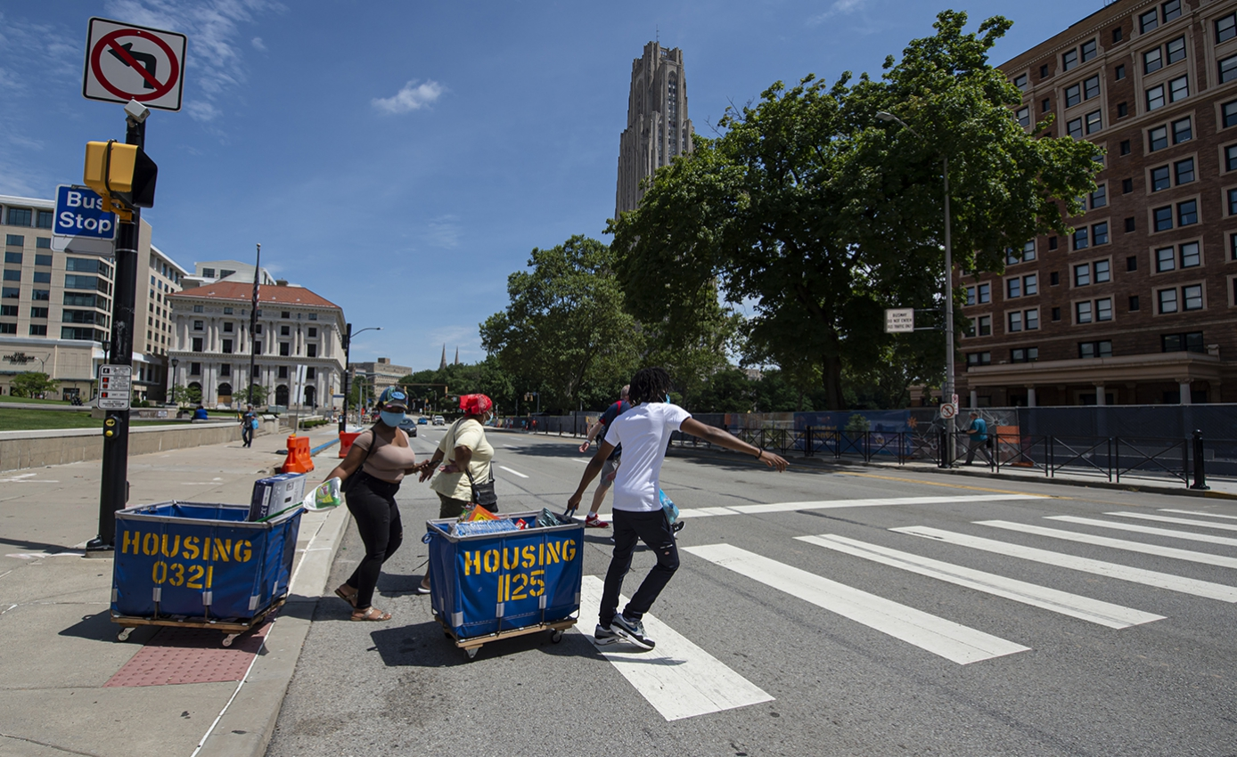 Students pull moving carts across a street