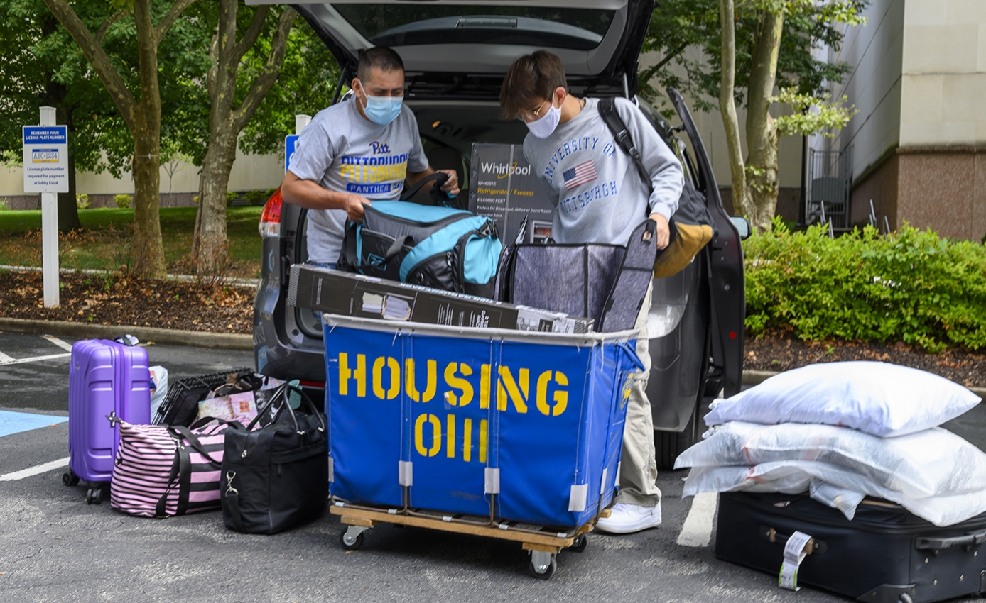 Two men load luggage into a moving cart
