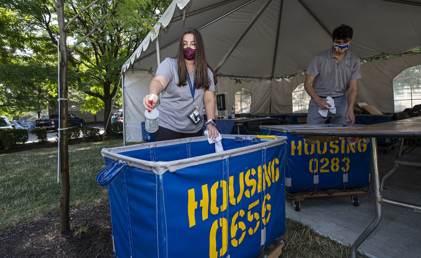 Two people spray moving carts in a tent