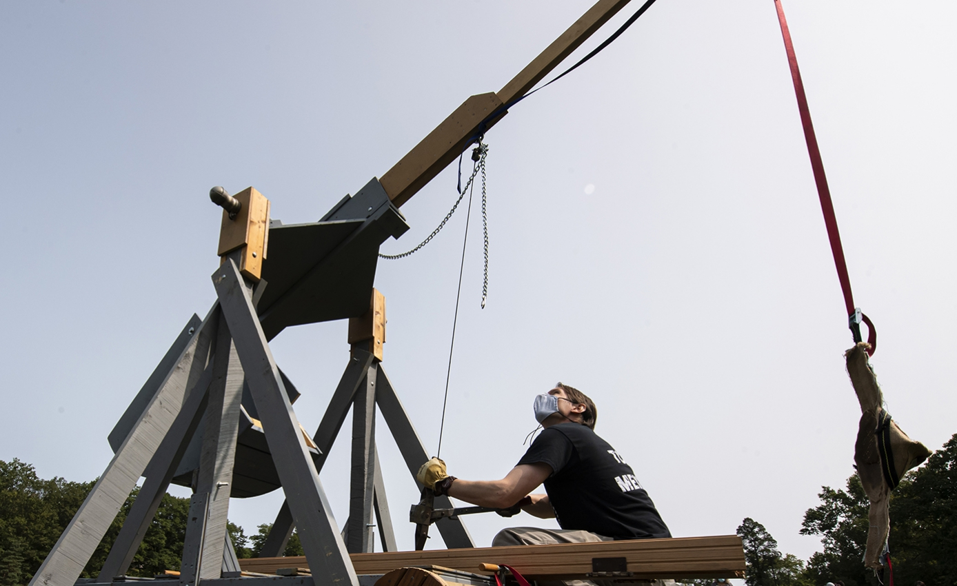 A person in a face mask readies a trebuchet