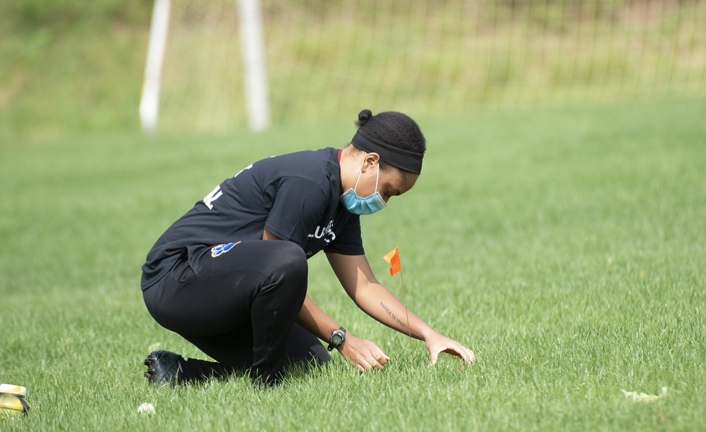 A person in all black and a face mask kneels in the grass