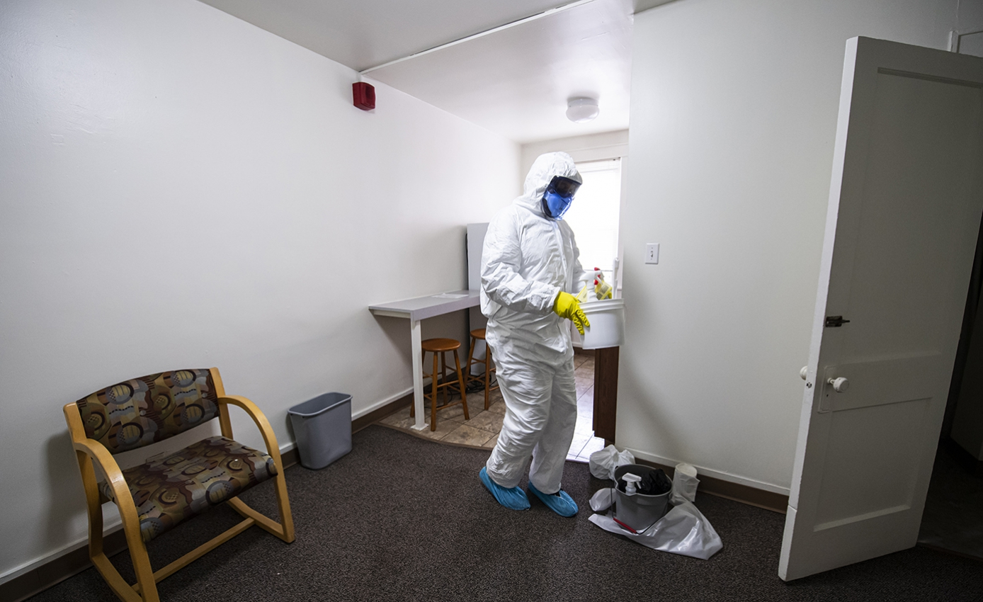 A man in white protective hear restocks cleaning supplies in a room with all white walls