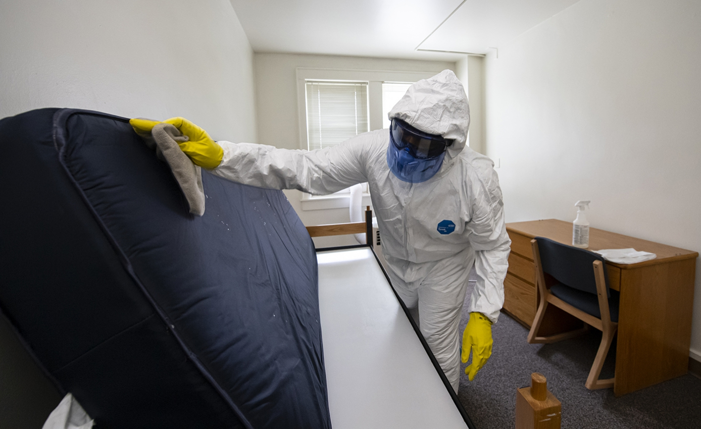 A man in all white protective gear cleans the bottom of a mattress