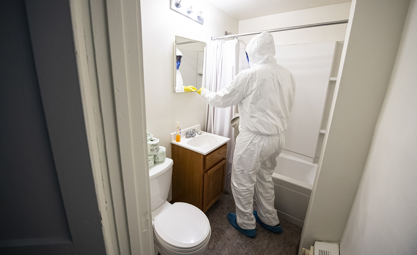 A man cleans the mirror of a bathroom in all white protective gear