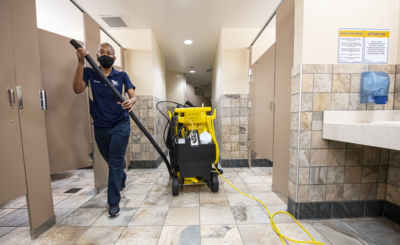 A woman in blue Pitt gear prepares to clean a tiled bathroom with a yellow machine