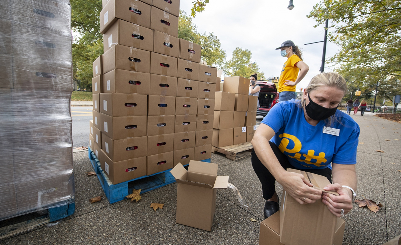 Two people in Pitt shirts preparing cardboard boxes