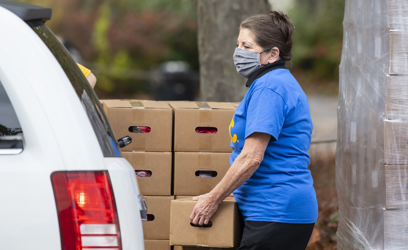 A person in a blue Pitt shirt and face mask loads a cardboard box into a white car