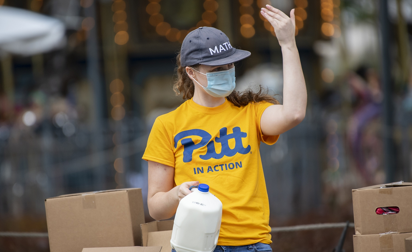 A person in a yellow Pitt shirt, cap and face mask holds a jug of milk and waves
