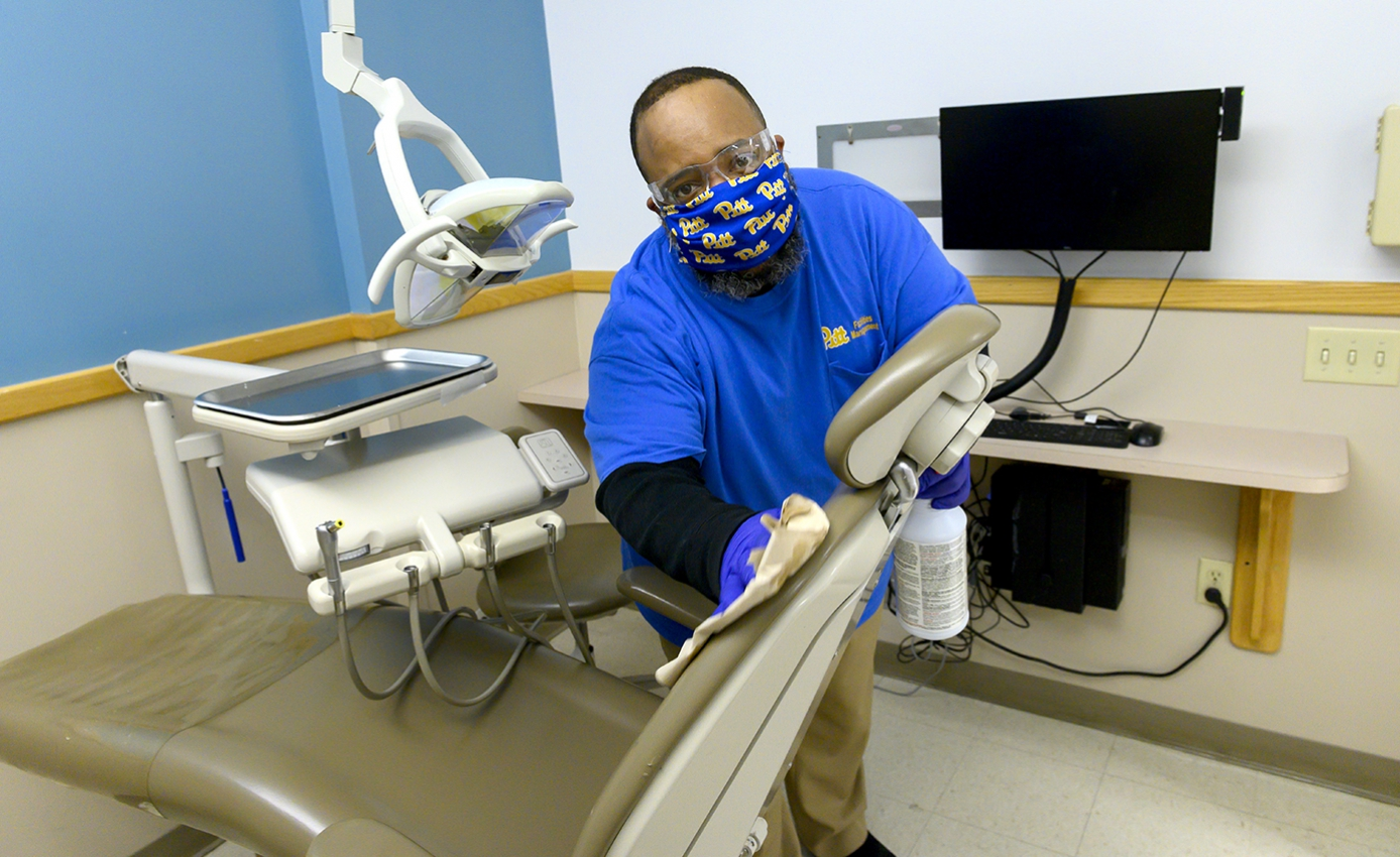 A man in blue Pitt gear cleans a dentist's chair5