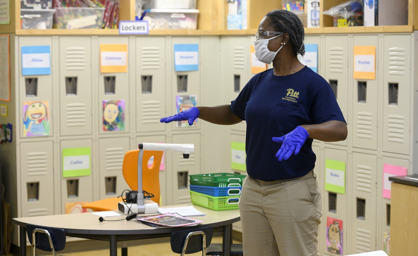 A person in a dark blue Pitt shirt, blue gloves and a face mask, stands in a kindergarten classroom in front of the lockers