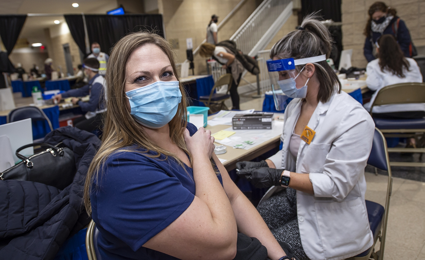 A person in a surgical face mask and a blue shirt prepares to receive a vaccination