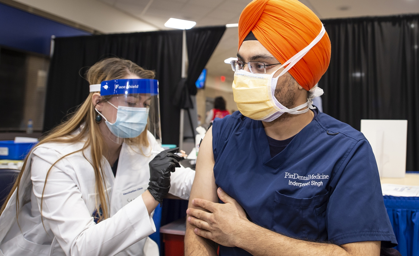A person in a yellow face mask, orange turban and blue shirt receives a vaccination