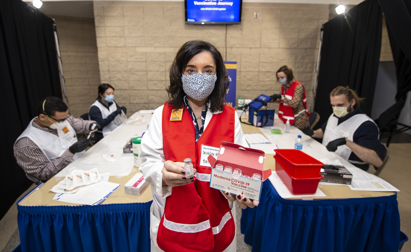 A person in a face mask and red vest holding vaccinations