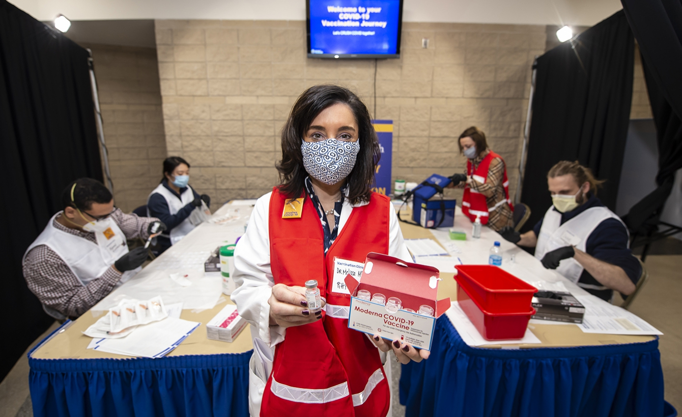 Melissa McGivney in a red jacket holds Moderna Vaccine in front of a table with four other members of the PittCoVax team