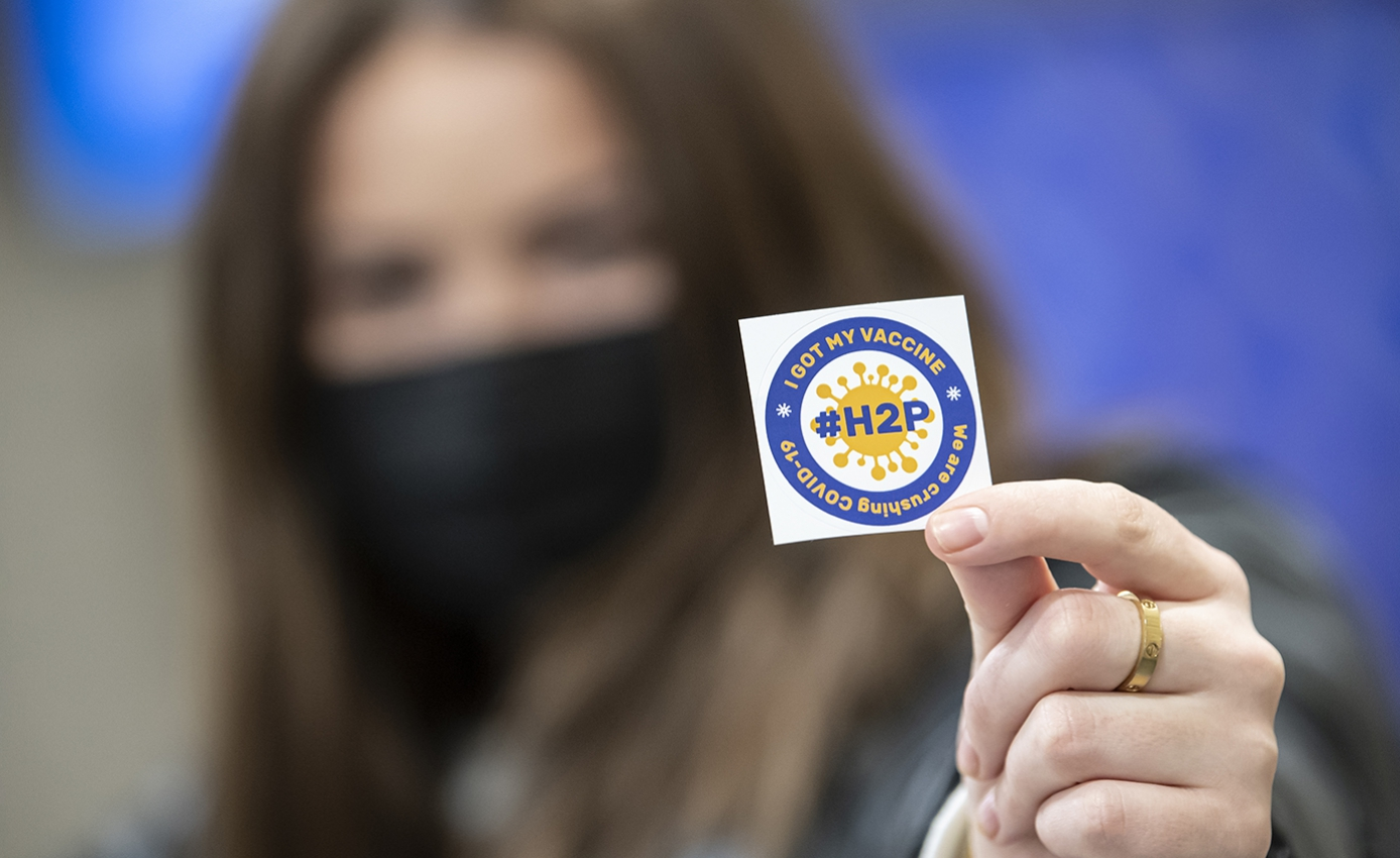 """A person in a black face mask holds up a sticker that reads, """"I got my vaccine."""""""