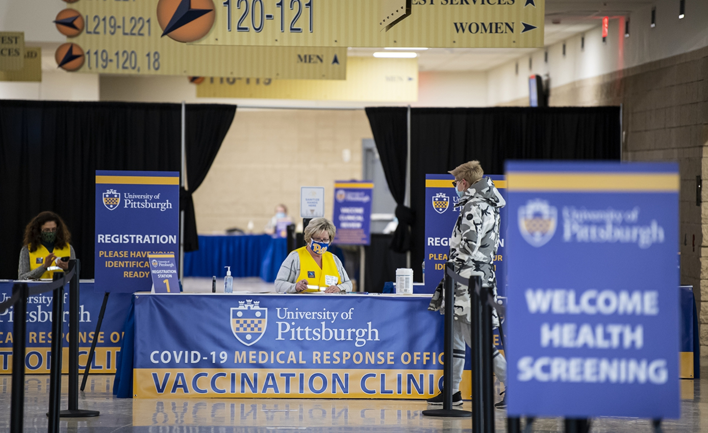 """A person in a face mask and yellow vest at a table reading """"COVID-19 Medical Response Office—Vaccination Clinic"""""""