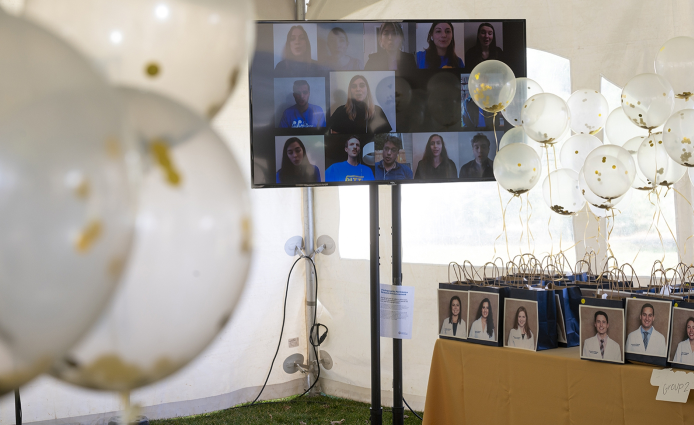 A television screen displaying people singing behind a table with gift bags with students' photographs on them