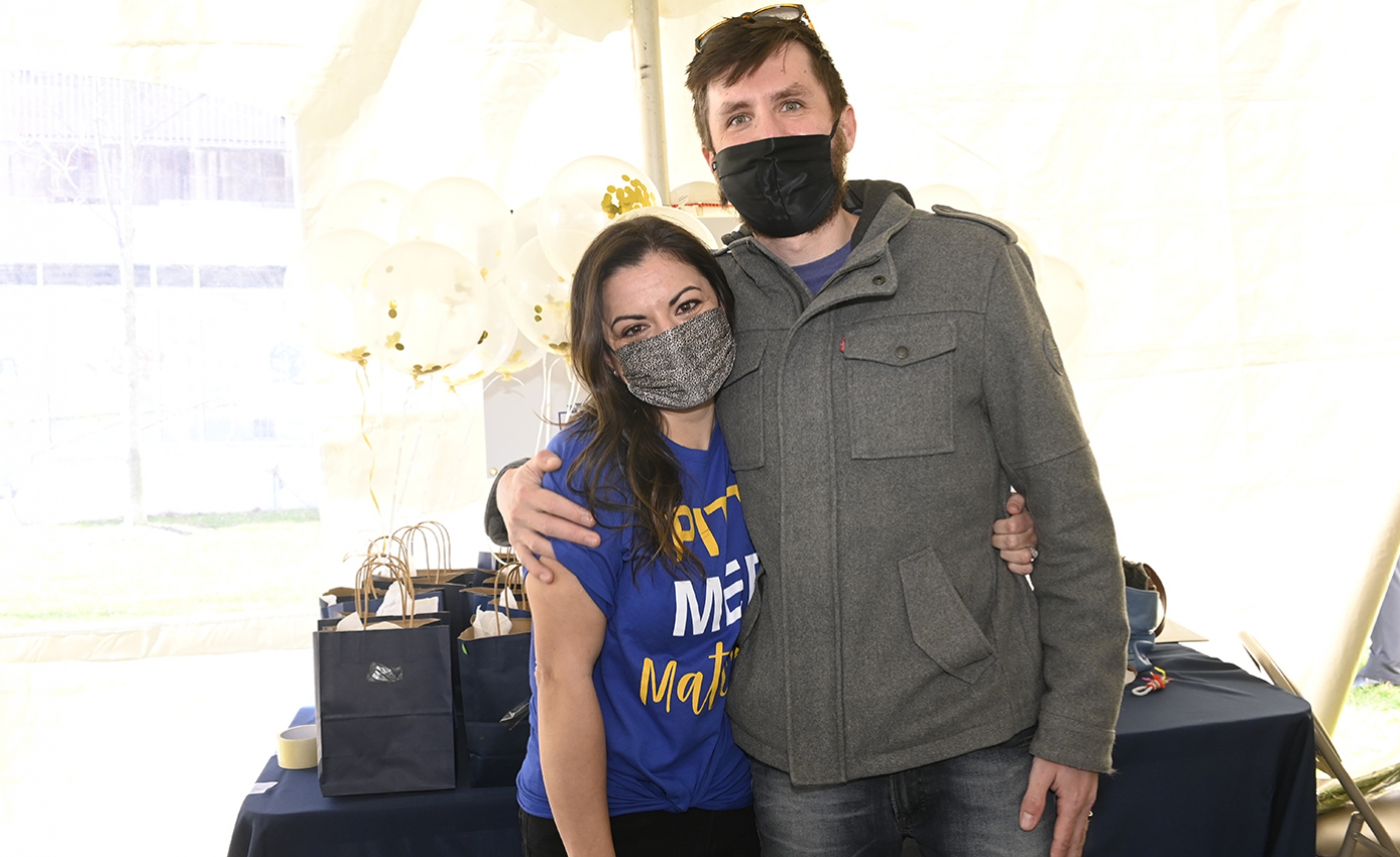 Jenny Perez in a blue Match Day T-shirt hugging her husband in a gray sweater in front of a table with gift bags on it
