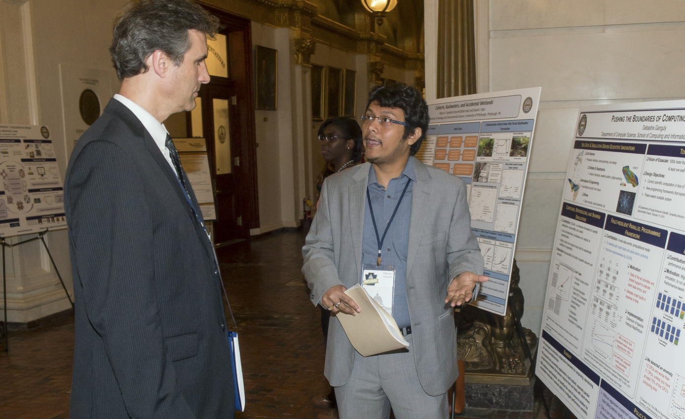 a man in a gray suit and blue collar shirt standing in front of a poster, talking to an onlooker