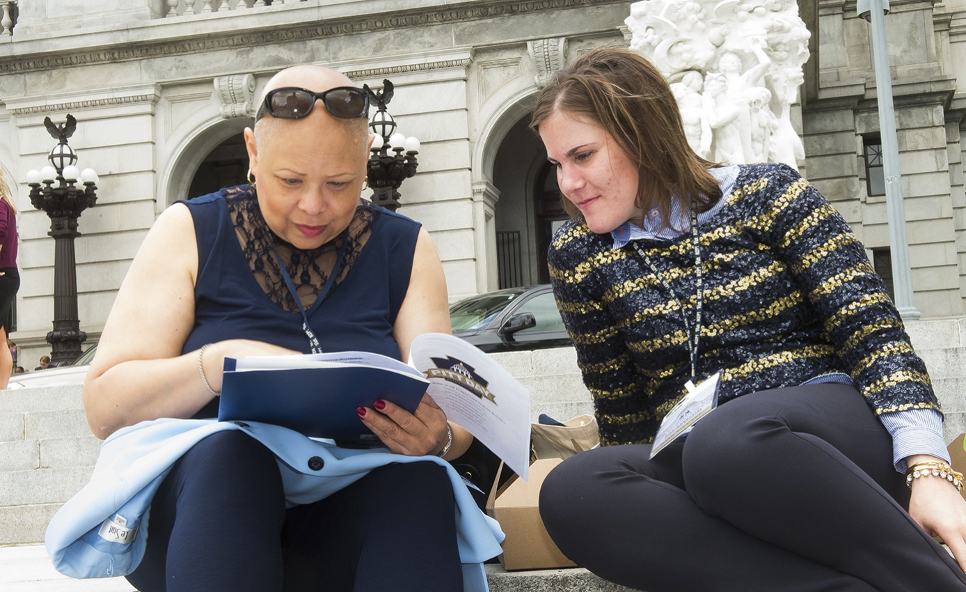 two women, one holding stapled papers, sit on steps outside, looking at the papers