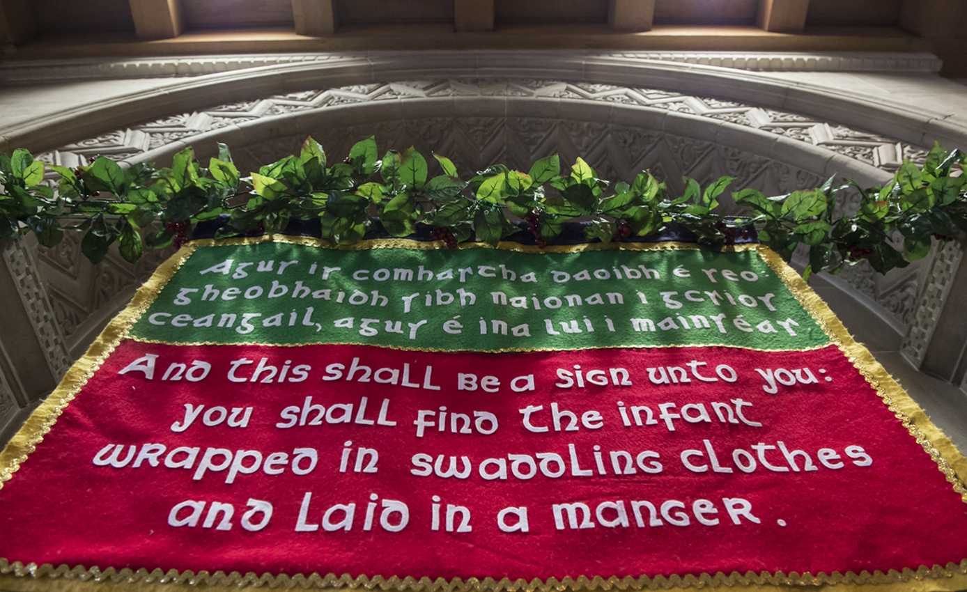A red and green fabric sign with Scripture written on it