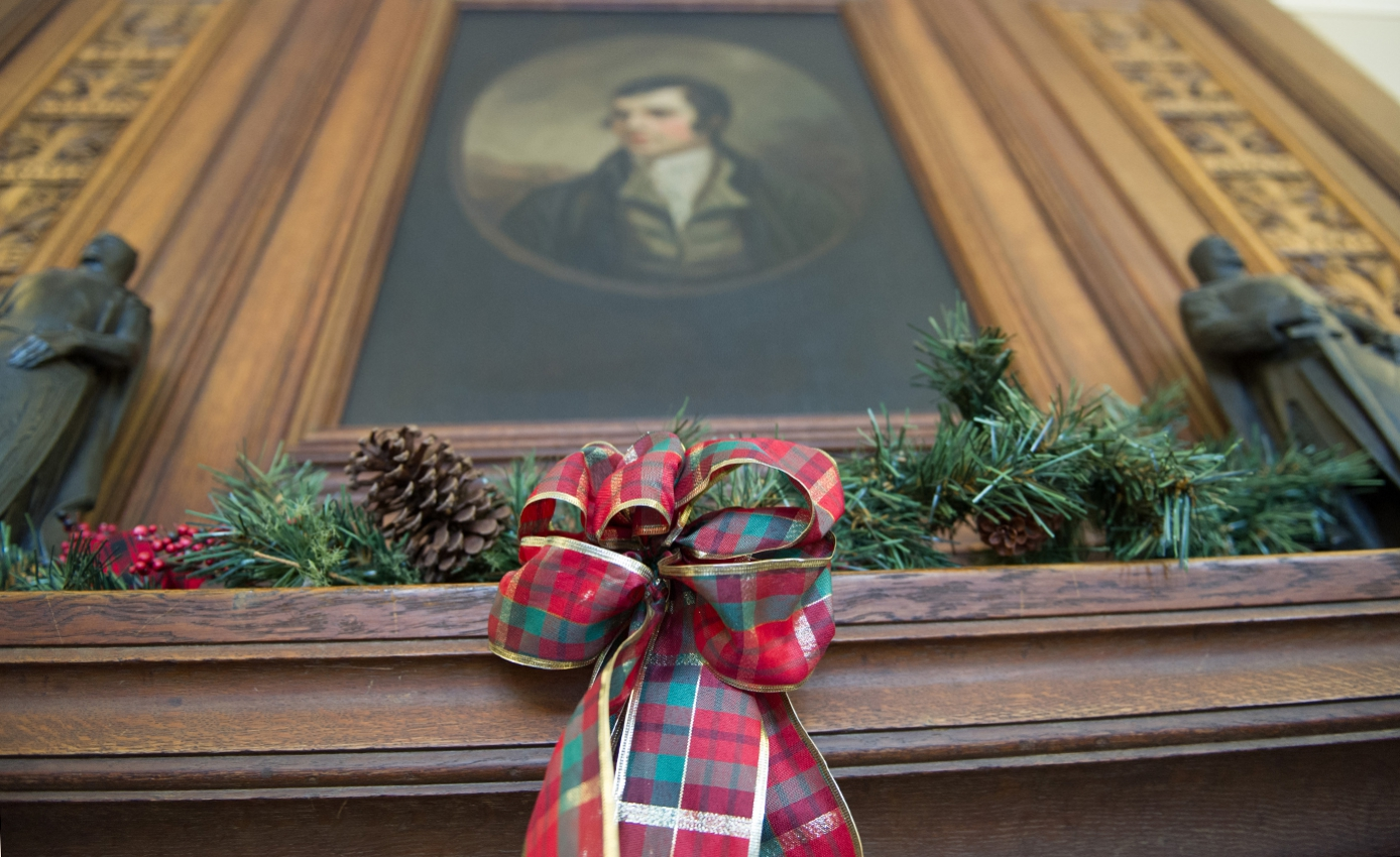 A plaid bow on a mantle covered with green