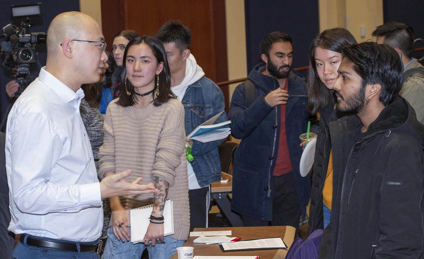 a group of audience members approach a panelist to ask more questions after the event