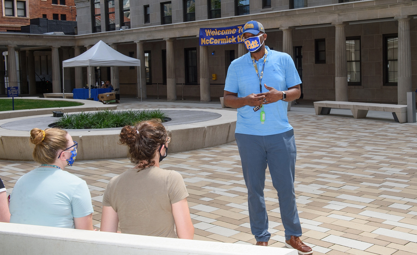 A man in a blue shirt and pants and face masks speaks with students