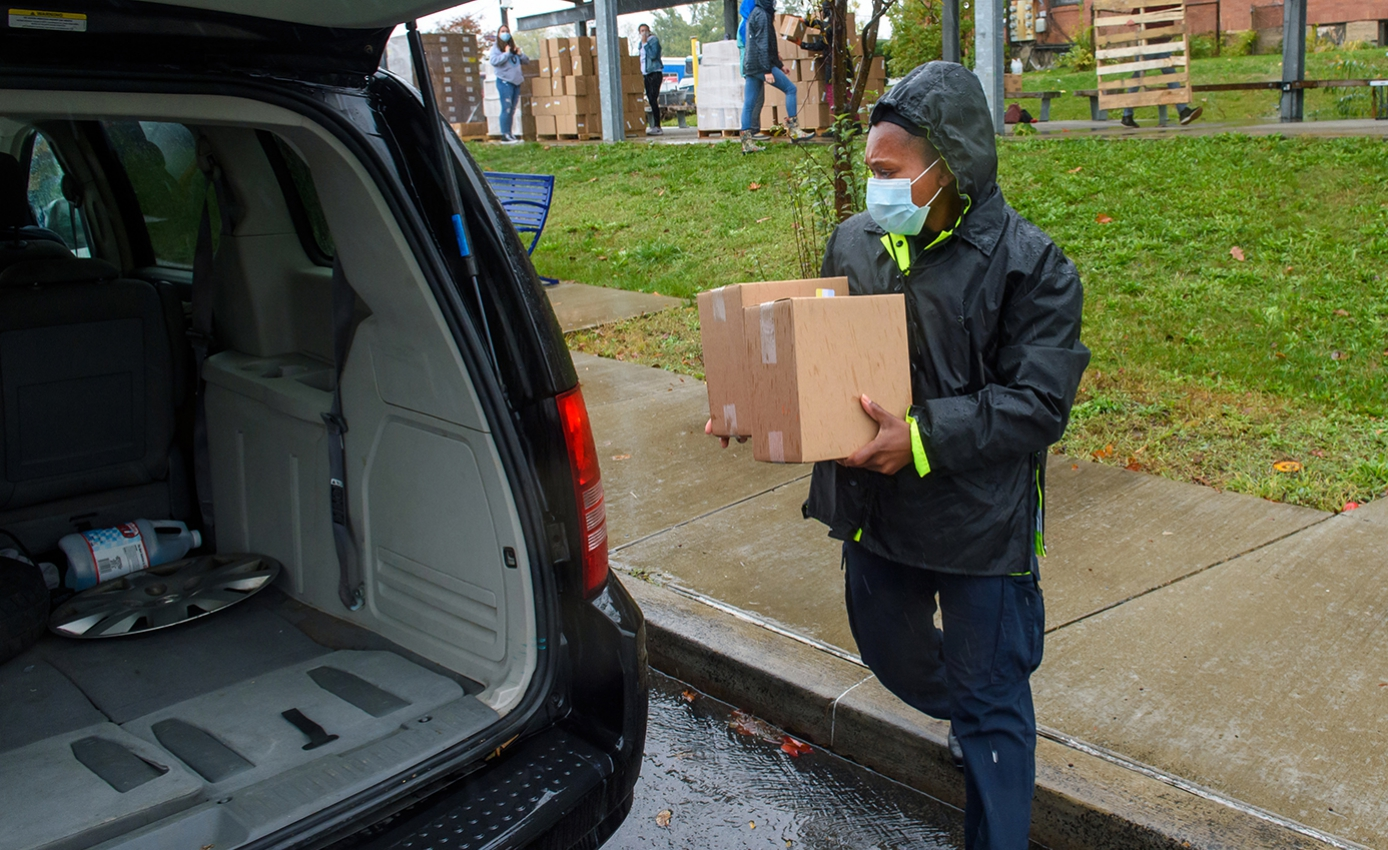 A person in a rain jacket and face mask holding cardboard boxes loads them into a van
