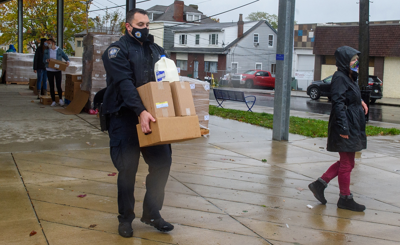 A police officer holds a pile of cardboard boxes and a jug of milk on a rainy sidewalk