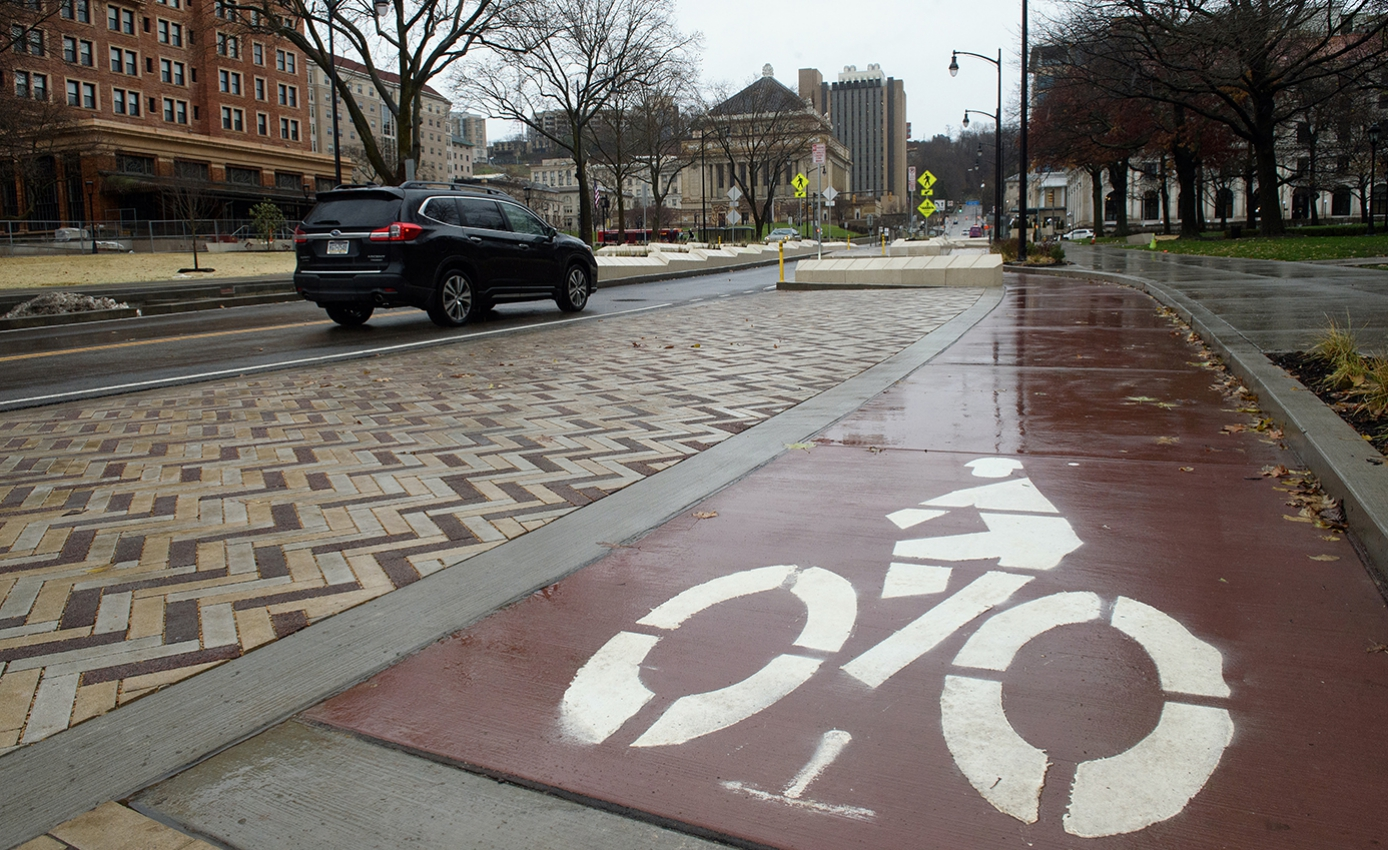 A cobblestone street with a bike lane with a black SUV driving down the center lane