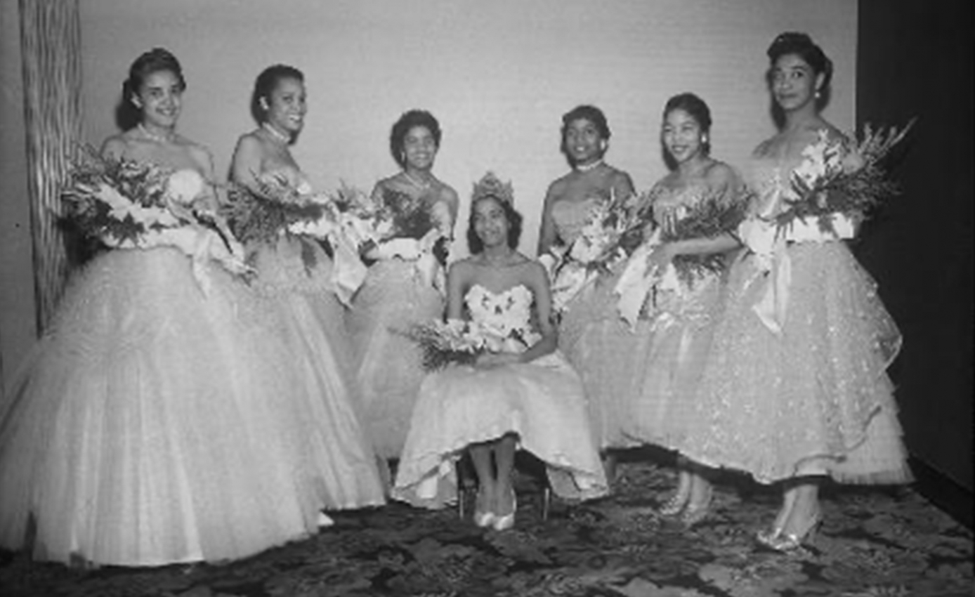 A black and white photo of seven women in dresses carrying flowers