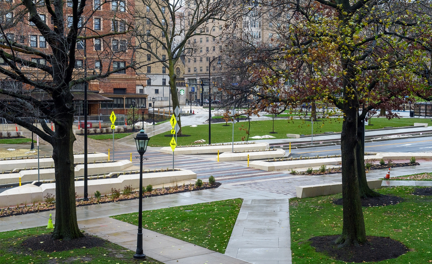 A side view of a completed street project, through trees and over a lawn