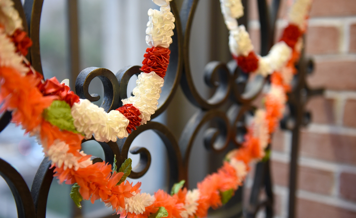 An orange, green, red and white wreath on an iron gate